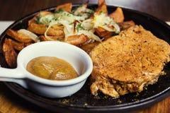 猪肉牛排用油煎的土豆在被服务的煎锅服务机智 免版税图库摄影