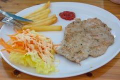 猪肉牛排用炸薯条和沙拉 免版税库存照片