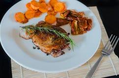 猪肉牛排用烤红萝卜和干蕃茄 免版税库存图片