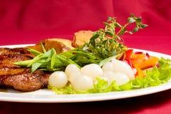 猪肉牛排用被烘烤的土豆 免版税库存照片