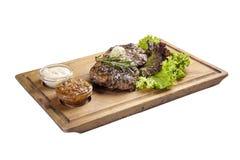 猪肉牛排用调味汁和绿色 在whiteboard和白色背景 免版税库存照片