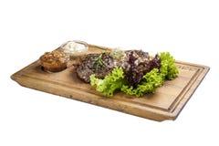 猪肉牛排用调味汁和绿色 在whiteboard和白色背景 免版税库存图片