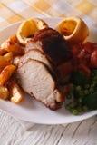 猪肉用土豆、新鲜蔬菜和约克夏布丁, vert 免版税库存图片