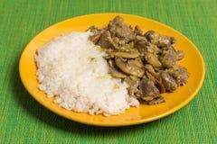 猪肉用蘑菇和煮沸的米在黄色板材 免版税图库摄影