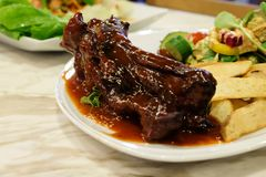 猪肉裂口烤肉牛排服务用炸薯条和有机沙拉配菜 免版税库存图片