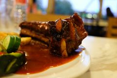 猪肉裂口烤肉牛排服务用炸薯条和有机沙拉配菜 库存图片
