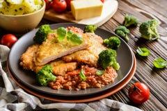 猪肉Piccata用西红柿酱和蒸的硬花甘蓝和煮的土豆 库存照片