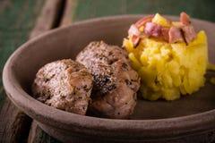猪里脊肉的两个部分在黏土板材的用土豆 免版税库存照片