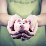 猪钱箱在妇女手上 免版税库存照片
