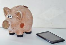 猪贪心银行和智能手机 免版税库存照片