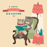 猫和小猫阅读书 免版税库存照片