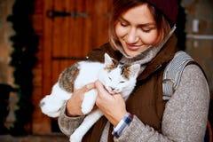 猫在女孩志愿者的手上,无家可归的动物的风雨棚的 宠物 图库摄影