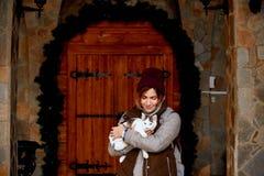 猫在女孩志愿者的手上,无家可归的动物的风雨棚的 宠物 免版税库存照片