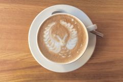 猫头鹰拿铁艺术浓咖啡在一张木桌上的杯子热奶咖啡在咖啡馆 免版税库存图片