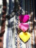 猫尾巴和五颜六色的心脏在圣诞节毛线衣 免版税库存照片
