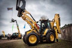 猫拖拉机和其他建筑器材在里加机械销售公开事件  免版税库存图片