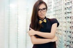 戴猫眼框架眼镜的典雅的Bowtie妇女在光学商店 库存图片