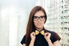 戴猫眼框架眼镜的典雅的Bowtie妇女在光学商店 库存照片