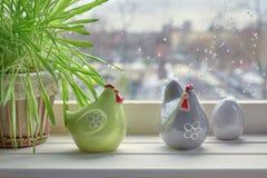 猫草和两只陶瓷母鸡用鸡蛋在一windowboard在镭 库存照片