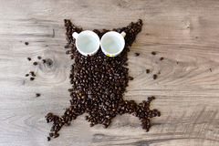 猫头鹰塑造了从咖啡豆和两个空的浓咖啡杯子做的图在桌顶部 库存照片