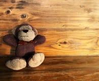 猴子在木桌上的玩偶微笑 免版税图库摄影