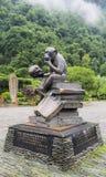 猴子坐拿着一个人的起重机雕象的书在黄色龙洞,张家界,湖南,中国的庭院 免版税库存图片