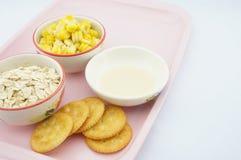 玉米、燕麦、薄脆饼干和变甜的浓缩牛奶在桃红色盘子 免版税库存图片