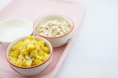 玉米、燕麦和糖在桃红色盘子 免版税库存图片