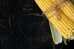 玉米两个玉米棒在一张黑木桌上的 库存照片