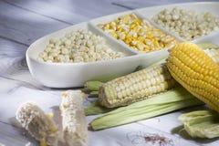 玉米棒子和黄色谷核在白色玻璃花瓶在白色木背景玉蜀黍属5月 免版税库存图片