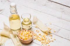 玉米油和玉米在土气木背景 免版税库存照片