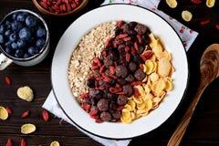 玉米片、巧克力球、燕麦粥、goji莓果和新鲜的蓝莓健康早餐  图库摄影