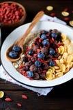 玉米片、巧克力球、燕麦粥、goji莓果和新鲜的蓝莓健康早餐  库存照片