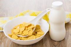 玉米片和匙子在白色碗,瓶酸奶 图库摄影