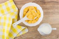 玉米片和匙子在白色碗,水罐牛奶 免版税库存照片