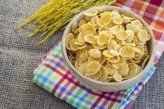 玉米片和黄色米有大袋或桌布背景 免版税图库摄影