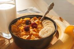 玉米片在碗的早餐谷物有杯的牛奶、莓果和香蕉在木桌上 免版税库存照片