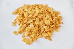 玉米片堆在被绘的白色木背景的 在一张木桌上驱散的玉米片 免版税库存图片