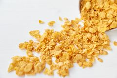 玉米片存放人与一个金属碗的在被绘的白色木背景 在一张木桌上驱散的玉米片 库存照片