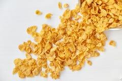 玉米片存放人与一个金属碗的在被绘的白色木背景 在一张木桌上驱散的玉米片 免版税库存照片