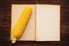 玉米穗和开放书 免版税图库摄影