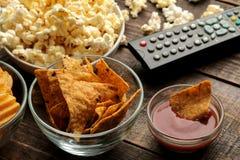 玉米粉薄烙饼和玉米花,电视遥远在棕色木背景 电影的概念在家 特写镜头 免版税库存照片