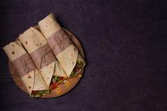 玉米粉薄烙饼,面卷饼,三明治扭转了卷 套用牛肉、蕃茄、莴苣、黄瓜、切达干酪、玉米和洋葱圈 图库摄影