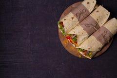 玉米粉薄烙饼,面卷饼,三明治扭转了卷 套用牛肉、蕃茄、莴苣、黄瓜、切达干酪、玉米和洋葱圈 免版税库存图片