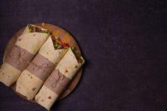 玉米粉薄烙饼,面卷饼,三明治扭转了卷 套用牛肉、蕃茄、莴苣、黄瓜、切达干酪、玉米和洋葱圈 免版税库存照片