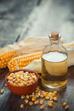 玉米精油瓶、种子在碗和两个棒子 免版税库存照片