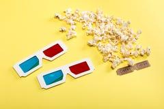 玉米花、戏院票和3D玻璃在黄色,电影放映时间概念 库存照片