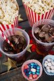 玉米花、糖果店和饮料在与7月4日题材的木桌上安排了 免版税库存照片