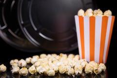 玉米花和一个电影角色在黑色、概念戏院和t前面 库存图片