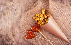 玉米花和两棒棒糖包裹以心脏的形式在老木背景 免版税图库摄影